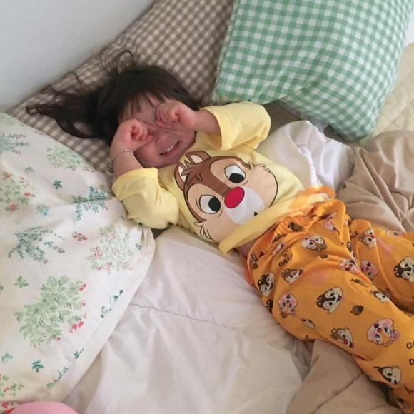 A baby lying on a bedDescription automatically generated